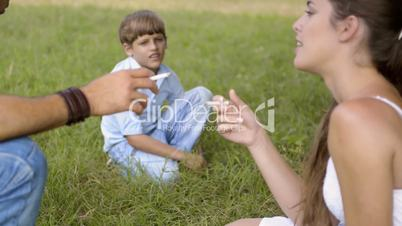Little boy looking at parents smoking cigarette and talking