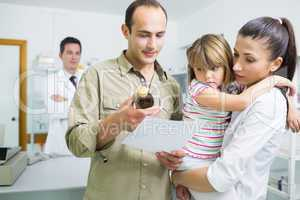 Family looking at medicine and a prescription in a pharmacy
