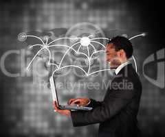 Man in suit working with laptop against a background