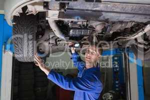 Mechanic with flashlight under car