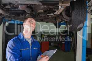Mechanic writing on clipboard in workshop