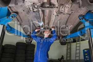 Mechanic inspecting car using flashlight