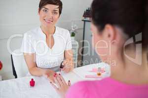 Young woman applying nail varnish to finger nails