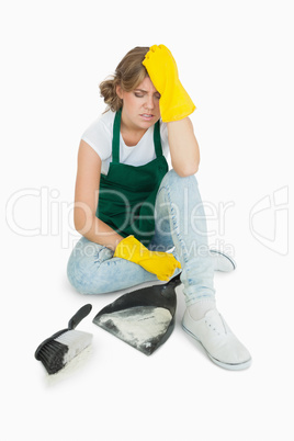 Tired young maid sitting with brush and dust pan