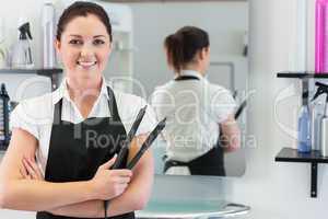 Female hairdresser holding hair straightener