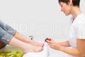 Woman applying nail varnish to toe nails at spa center