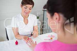 Nail technician applying nail varnish to finger nails