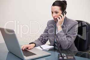 Shocked business woman using laptop while on call