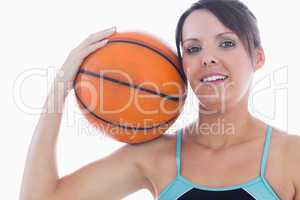 Portrait of happy woman holding basketball on shoulder