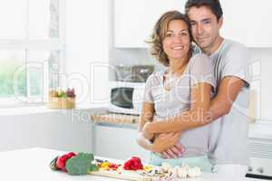 Wife and husband embracing in the kitchen