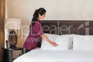 Smiling hotel maid fixing pillows
