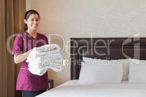 Hotel maid holding pile of fresh towels