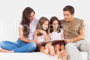 Family reading a story on a sofa