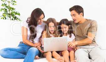 Family posing on a sofa with the laptop