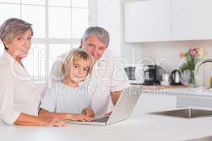 Child and grandparents looking at camera with a laptop