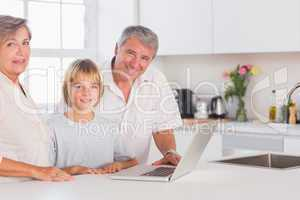 Child and grandparents looking at the camera with a laptop in fr