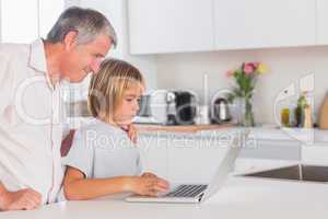 Child and grandfather looking at laptop