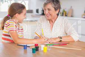 Child with her granny drawing and laughing