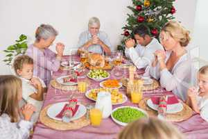 Family saying grace before christmas dinner