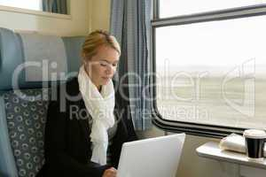 Woman using laptop traveling by train commuter