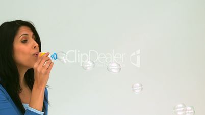 Cute woman blowing bubbles