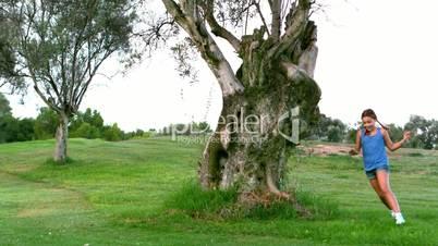 Girl running around a big tree