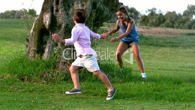 Two children running around a big tree