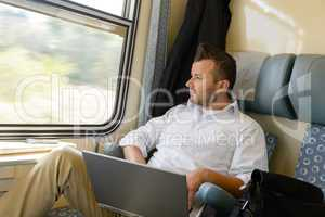 Man looking out the train window laptop
