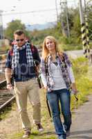 Couple walking with backpack in train station