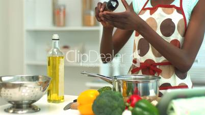 Woman adding pepper to saucepan