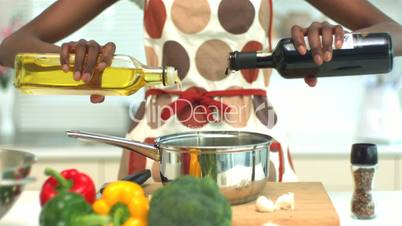 Woman adding oil and vinegar to saucepan