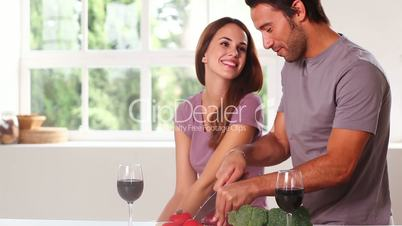Smiling couple with red wine chopping vegetables