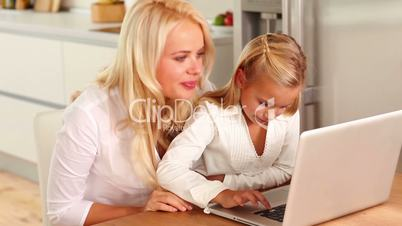 Mother and daughter using laptop at kitchen table