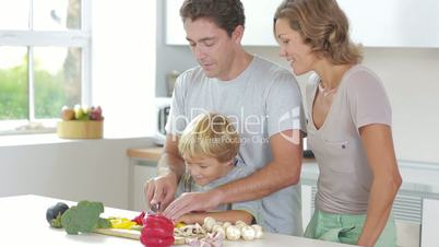 Father teaching son to slice vegetables