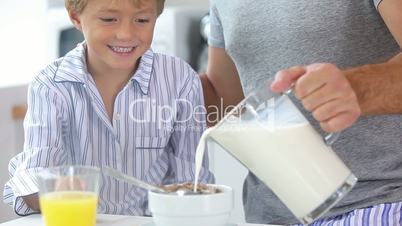 Father pouring milk for sons cereal