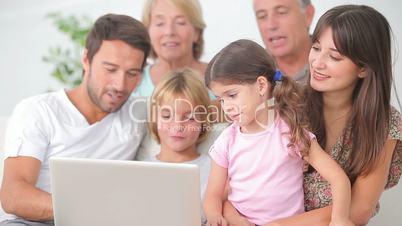 Smiling family watching something on laptop