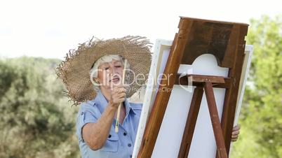 Old woman painting in the park
