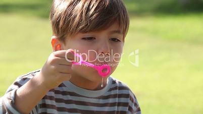 Little boy has fun blowing bubbles