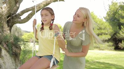 Mother pushing daughter on the swing