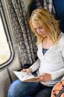 Woman traveling by train and reading book
