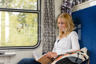 Woman reading book in train smiling commuter