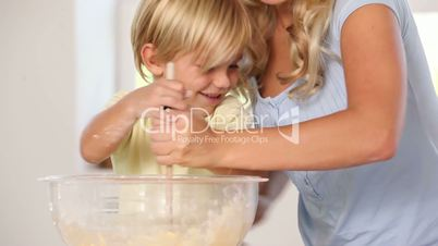 Mother and son mixing pastry in a bowl
