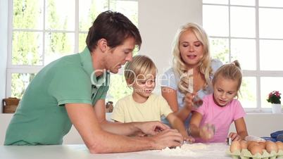 Parents kneading a dough with their children