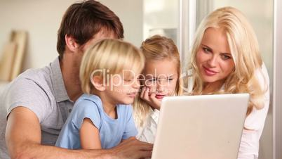 Parents and children talking and using a laptop