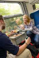 Couple traveling by train eating sandwiches hungry
