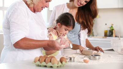 Grandmother child mother preparing the dough