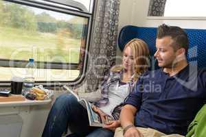 Couple traveling by train reading magazine smiling