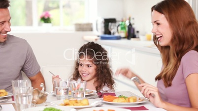 Family laughing at dinner table