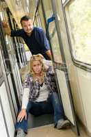 Woman and man sitting on train hallway