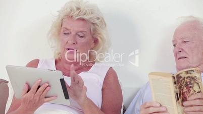 Old couple using a tablet and book